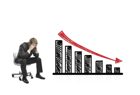sad businessman sitting on chair with falling graph