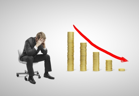 regretful: sad businessman sitting on chair with falling money graph