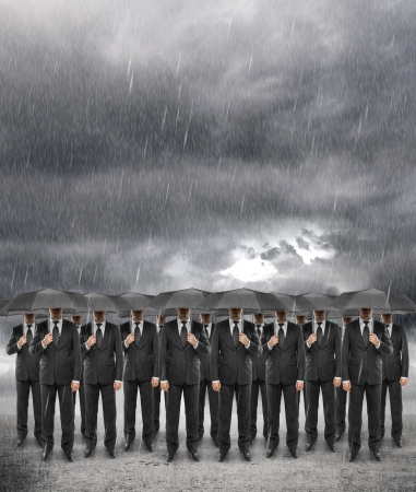 uomo sotto la pioggia: squadra di affari in piedi con l'ombrello in tempesta