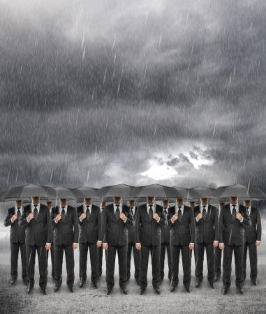 rain umbrella: team businessman standing with umbrella in storm