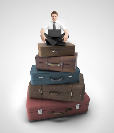 businessman sitting on travel bags   on a gray background photo