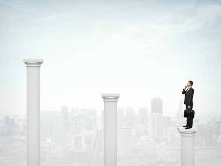 businessman standing on a column and talking on phone photo