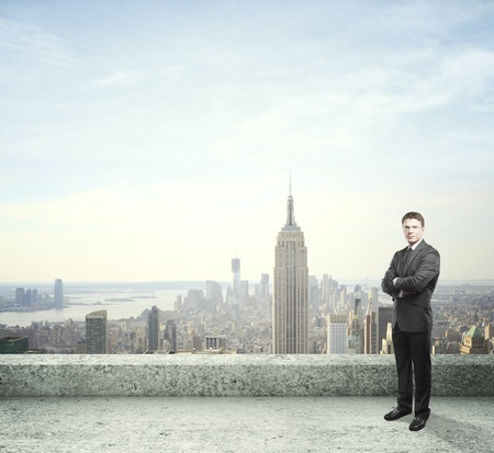 man standing on roof and city on back photo
