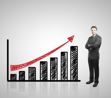 young businessman standing and drawing arrow graph photo