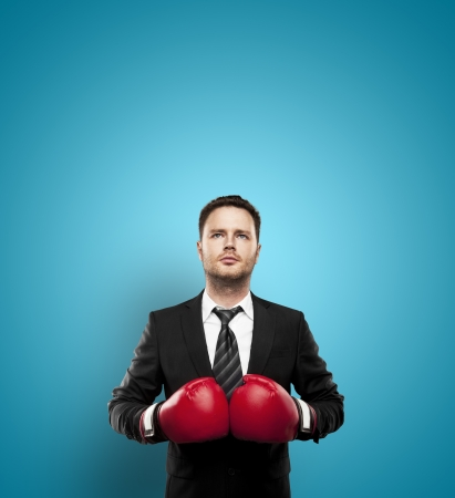 businessman in boxing gloves on a blue background Stock Photo - 20523238