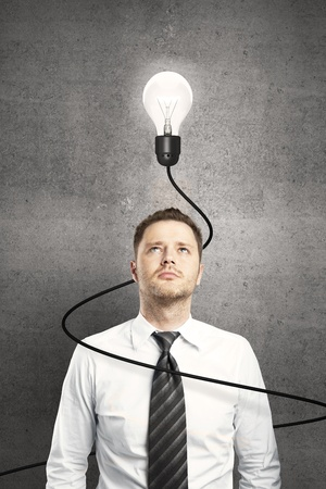 businessman: businessman and lamp with cable on concrete background Stock Photo