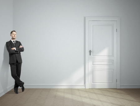 dreaming businessman standing in gray room photo