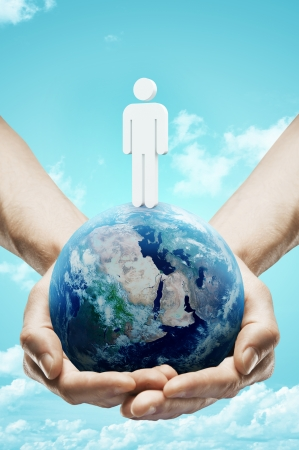 hands holding earth on sky background photo