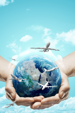 hands holding earth and airplane on sky background photo