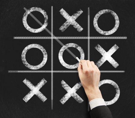 tic tac toe: hand drawing a game of tic tac toe on a black chalkboard Stock Photo