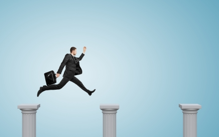 businessman jumping on a column, on a blue background Stock Photo - 20522937