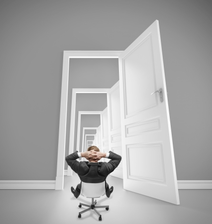 relaxing businnessman sitting on chair and looking in openet doors photo