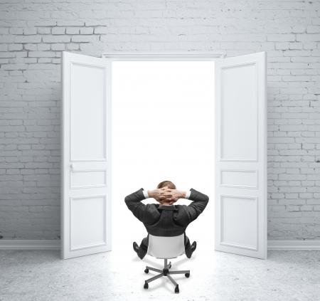 open doors: businnessman sentado en la silla en la habitación de ladrillo