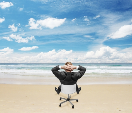 relaxing businnessman sitting on beach Stock Photo