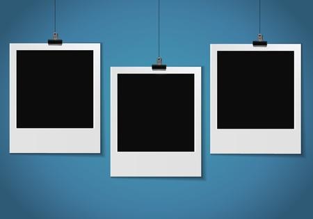 push pins: three blank photo pinned on blue wall