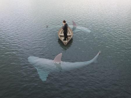 man thinking: jeune bateau de la pens�e de l'homme avec les requins autour de lui