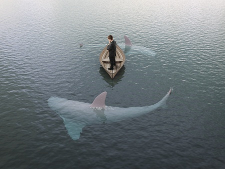 young man thinking  boat with sharks around him photo