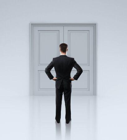 businessman standing: businessman standing in front of closed doors