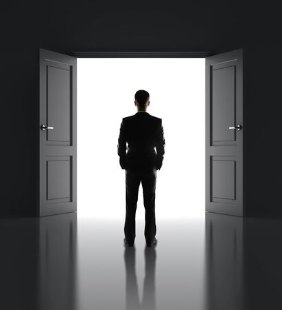 businessman standing in front of opened doors photo