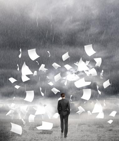 uomo sotto la pioggia: d'affari a piedi in caso di pioggia con volare intorno carta Archivio Fotografico