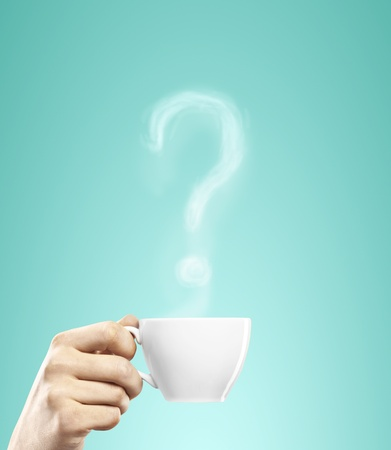 cup of coffee in hand with question mark photo