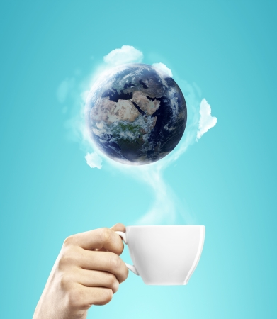 cup of coffee in hand with earth photo