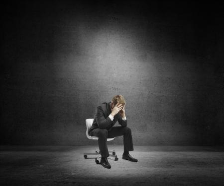 печальный: Грустно бизнесмен, сидя на стуле в бетонное помещение