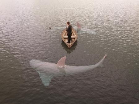 Mann denkt Boot mit Haien um ihn herum Standard-Bild - 20950877