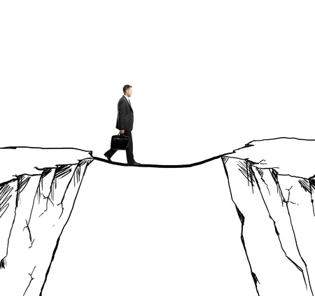 businessman walking on rope from rock to rock photo