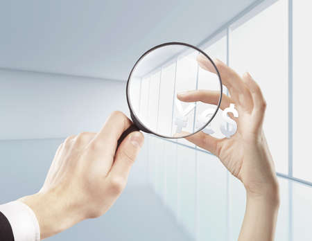 lupe: magnifying glassin hand  and  yen, dollar and euro Stock Photo