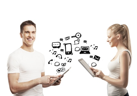 young man and woman holding pad with social icons Stock Photo