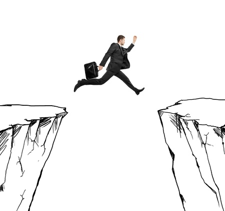 abyss: businessman jumping at drawing rock