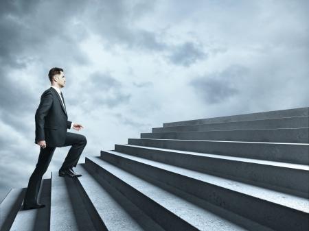 businessman walking near ladder in sky photo
