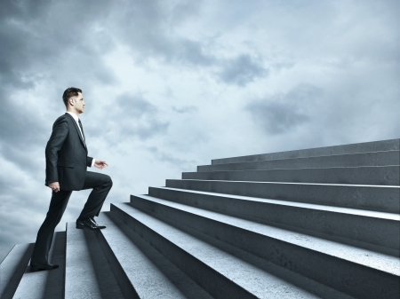 steps to success: businessman walking near ladder in sky