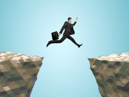 businessman with briefcase  jumping from mountain to mountain photo