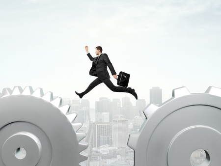 businessman jumping from one gear to another photo