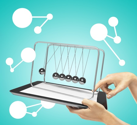 hands holding tablet with newtons cradle photo