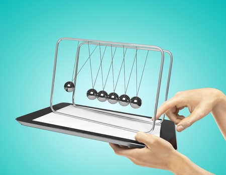 hands holding  touch pad with newton's cradle  on a blue background photo