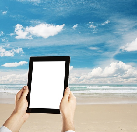 hands holding a tablet on beach photo