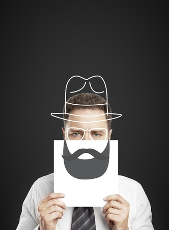 businessman holding paper with drawing beard and hat photo