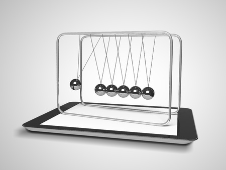 tablet and newton's cradle on a gray background photo