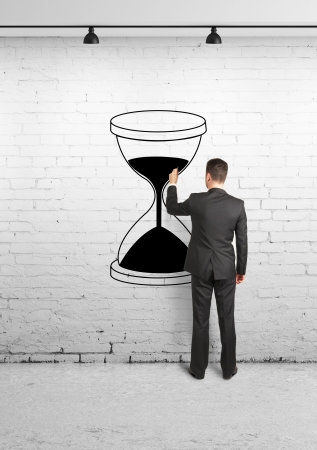 businessman drawing hourglass on brick wall photo