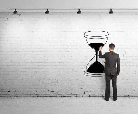 money time: young man drawing hourglass on brick wal Stock Photo