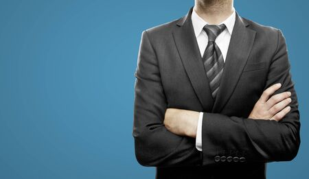young businessman standing  with hands  folded on blue background Stock Photo - 21284499