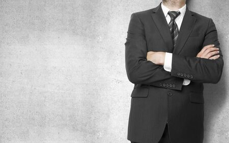 businessman standing  with hands  folded on concrete wall background Stock Photo - 21275635