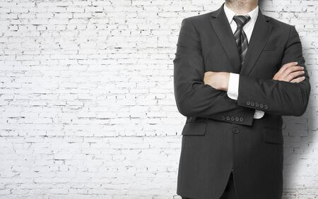 businessman standing with hands  folded on brick wall background Stock Photo - 21284502