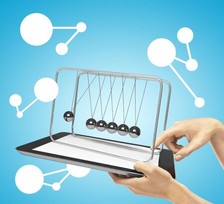 newton's cradle: hands holding tablet with newtons cradle Stock Photo