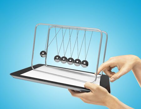hands holding  touch pad with newton's cradle photo