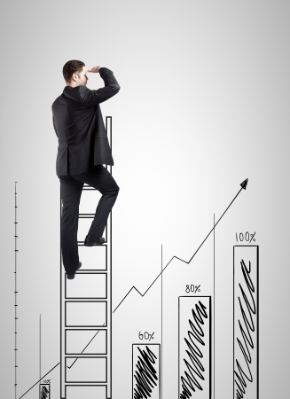 businessman climbing on ladder and looking on chart photo