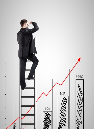 businessman climbing on ladder and looking on drawing chart photo